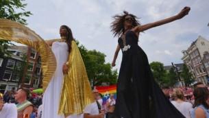 La chanteuse pop israélienne Dana International, à droite, à danser sur le bateau juif à la gay pride d'Amsterdam, le 2 août 2014 (Crédit : Cnaan Liphshiz / JTA)