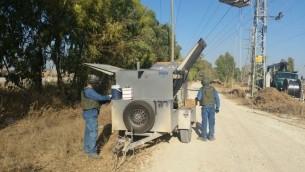Des employés de la CEI réparent des lignes électriques sur la frontière de Gaza, portant des casques et des gilets blindés (Crédit : Charlie Shriki, Courtesy de l'Israël Electric Corporation)