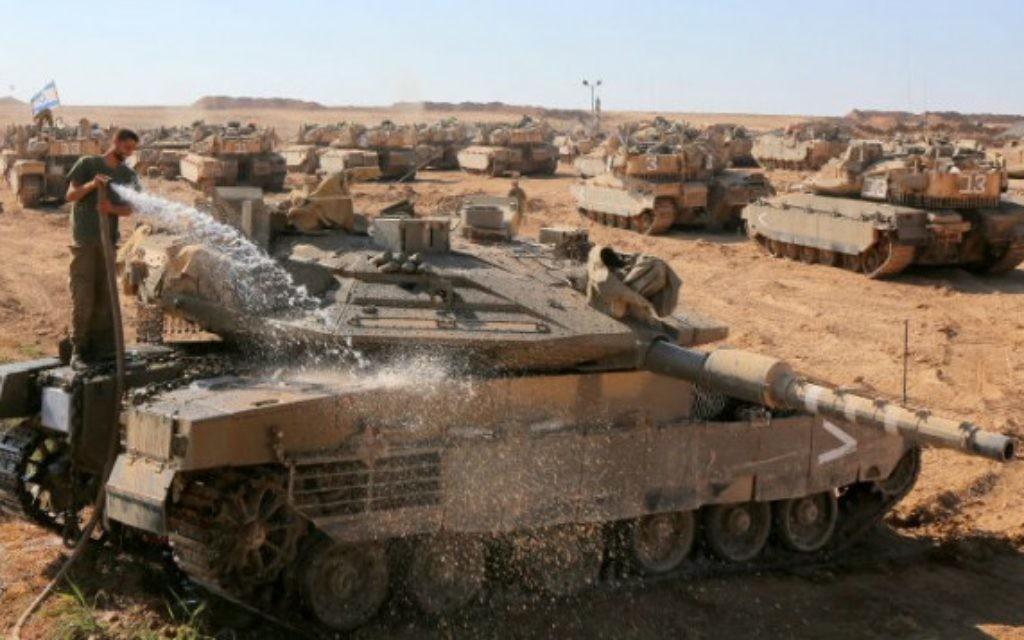 Un soldat israélien nettoie un tank de l'armée dans le sud d'Israël (Crédit : Edi Israel/Flash90))