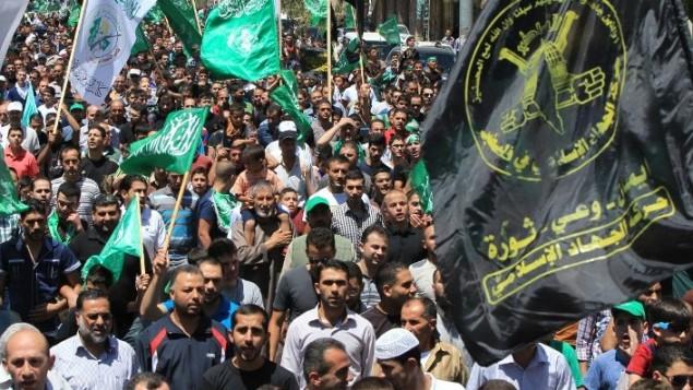 manifestants palestiniens avec des drapeaux du Hamas et du Jihad islamique le 8 août 2014 (Crédit : AFP/Hazam Bader)
