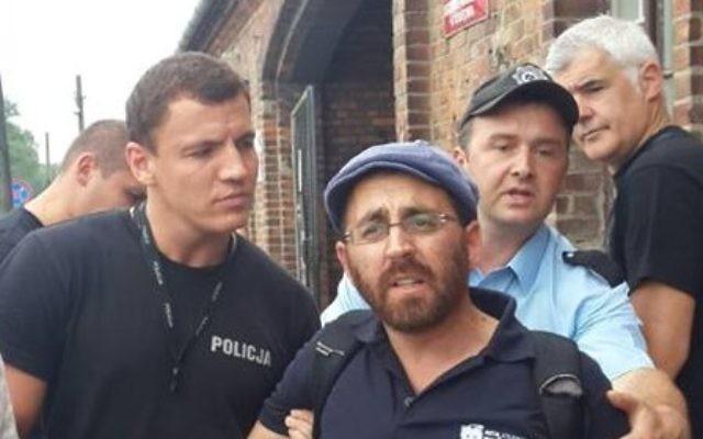 Rabbi Rafi Ostroff détenu par des gardes de sécurité à Auschwitz-Birkenau 1 Août 2014. (Crédit : La page Facebook de Rafi Ostroff)