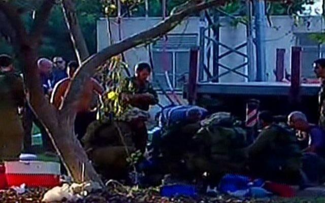 Les premiers intervenants et les soldats de Tsahal sur la scène d'un barrage de mortier dans le kibbutz Nirim dans la région d'Eshkol. (Crédit : capture d'écran Deuxième chaîne)