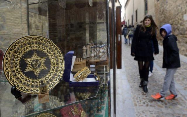 Illustration : des gens passent devant une boutique de souvenirs dans l'ancien quartier juif de Tolède, en Espagne, le 27 février 2014. (Crédit : AFP / Gerard Julien)