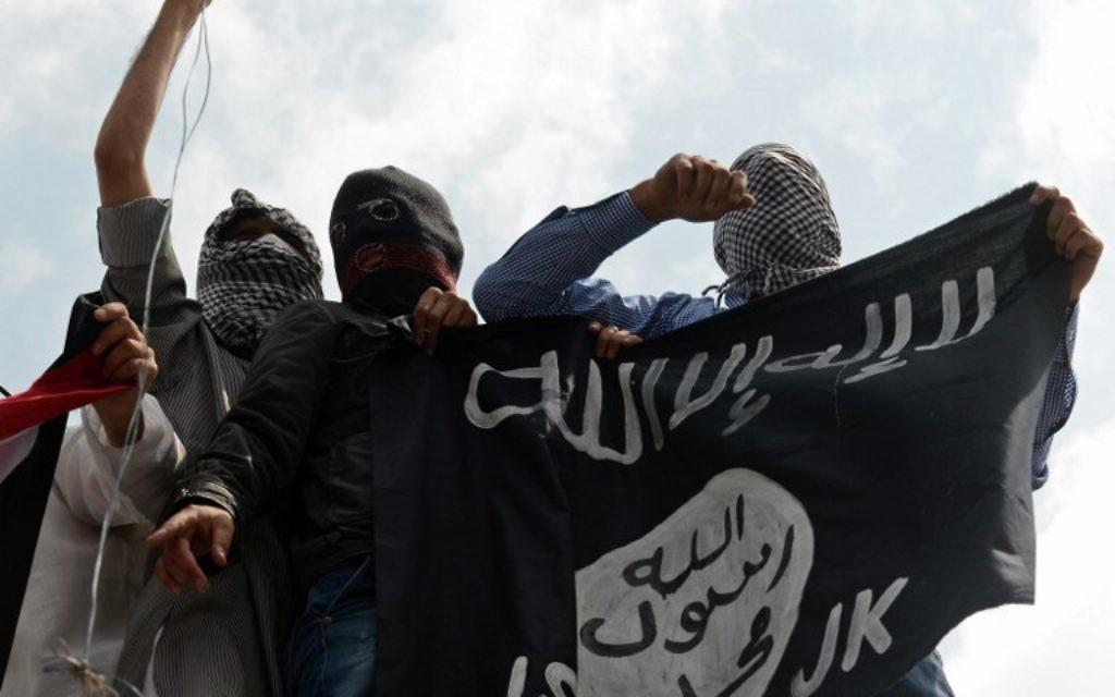 Des manifestants tiennent un drapeau de l'Etat islamique lors d'une protestation contre Israël, au centre de Srinagar, à Cachemire - le 18 juillet 2014 (Crédit : AFP / Tauseef MUSTAFA)