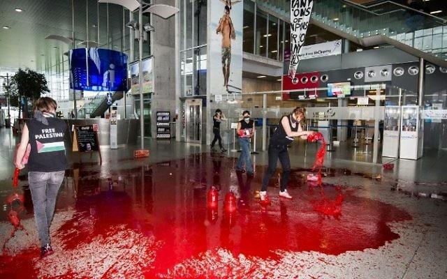 """Belgique : Des féministes déversent du faux sang dans un aéroport pour protester contre le """"transport d'armes vers Israël"""" - 26 ao^t 2014 (Crédit : AFP / BELGA / NICOLAS LAMBERT)"""