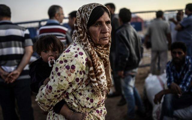 Une réfugiée kurde syrienne tient un bébé après avoir franchi la frontière près de la ville sud-est de la province de Sanliurfa Suruc, le 21 septembre, 2014 (Crédit : AFP PHOTO / BULENT KILIC)