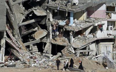 Une famille passe devant les ruines d'immeubles à Shejaiya, dans la bande de Gaza, le 27 août 2014. (Crédit : AFP/Roberto Schmidt)