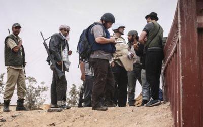 Steven Sotloff (au centre avec un casque noir) discutant avec des rebelles libyens, le 2 juin 2011.(Crédit : autorisation Etienne de Malgraive, via AFP)