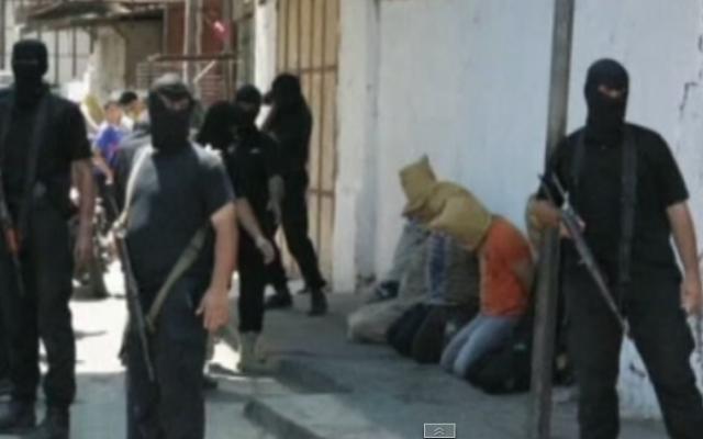 Des hommes armés du Hamas avec des collaborateurs présumés en août 2014 (Crédit : capture d'écran/YouTube/Euronews)