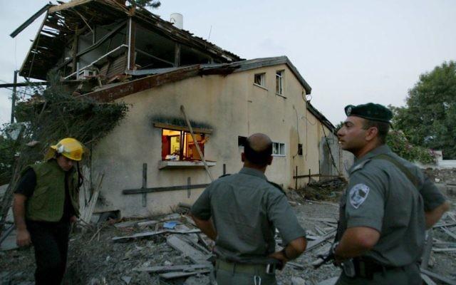Des forces de sécurité israéliennes inspectent les dommages à une maison après une attaque à la roquette Katioucha du Hezbollah dans le nord d'Israël à Nahariya, le 15 juillet, 2006 (Crédit photo: Pierre Terdjman / Flash90)