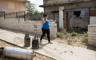 Une femme passe devant une maison à Sderot le 21 juillet 2014 (Crédit : Yonatan Sindel/Flash90)