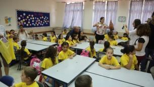 Des élèves de première année primaire sont accueillis à l'école primaire Ben Yehezkel à Ashkelon le premier jour de la nouvelle année scolaire, 1er septembre, 2014 (Crédit : Edi Israël / Flash90)