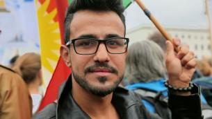 Mulsim Benno Bahman de Erbil, dans le Kurdistan irakien portait un grand drapeau kurde le 14 septembre, 2014 à la manifestation contre l'antisémitisme à Berlin. (Micki Weinberg / The Times of Israël)