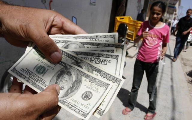 Un employé de l'AP montre l'argent qu'il vient de retirer du distributeur de la Bank of Palestine à Rafah le 8 juin 2012 (Crédit : Abed Rahim Khatib/Flash90)