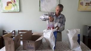 Un bénévole Vladimir prépare des sacs d'emballage de denrées alimentaires destinées aux clients. (JDC - Août 2014)