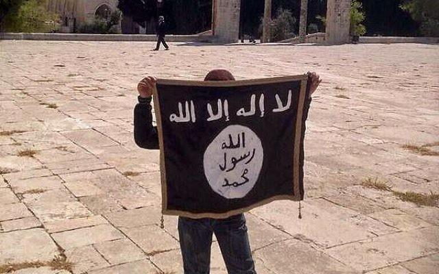 Un jeune adolescent tient un drapeau de l'Etat islamique sur le mont du Temple (Crédit : Facebook)
