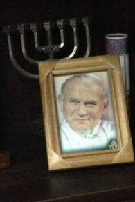 L'ancien prêtre juif garde une menorah à côté d'une photo du pape Jean-Paul II sur sa bibliothèque dans sa maison à Jérusalem. (Crédit : Renée Ghert-Zand / The Times of Israël)