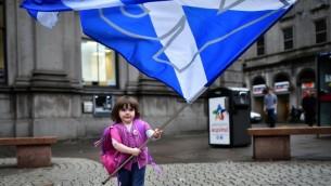 Un enfant joue avec un drapeau pro-indépendance du 'Oui' dans les rues d'Aberdeen en Ecosse, le 15 septembre 2014, avant le référendum sur l'indépendance de l'Ecosse. (Crédit : AFP PHOTO / BEN STANSALL)