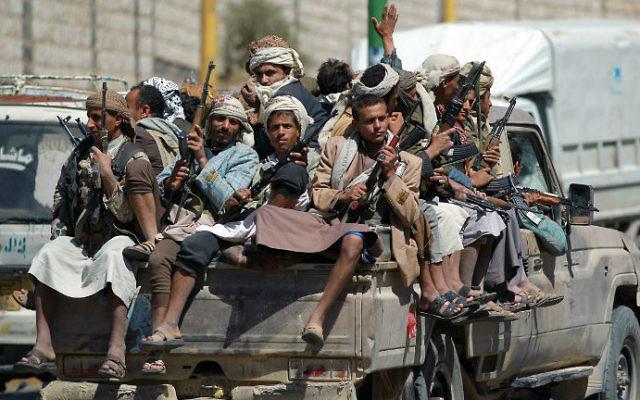 Des rebelles de l'armée yéménite chiite houthie anti-gouvernementaux sont assis à l'arrière d'un pick-up alors qu'ils roulent près de l'enceinte de la télévision d'Etat dans la capitale de Sanaa, le 21 septembre 2014 (Crédit : AFP / Mohammed Huwais)
