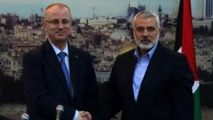 Le premier ministre de l'Autorité palestinienne Rami Hamdallah (à gauche) et l'ancien Premier ministre et dirigeant du Hamas à Gaza Ismail Haniyeh, le 9 octobre 2014 à Gaza (Crédit photo : Said Khatib/AFP)