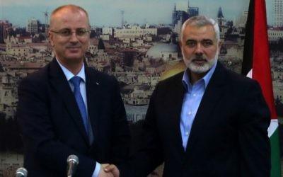 Le premier ministre de l'Autorité palestinienne Rami Hamdallah, à gauche, et l'ancien Premier ministre et dirigeant du Hamas à Gaza Ismail Haniyeh, à Gaza Ville, le 9 octobre 2014. (Crédit : Said Khatib/AFP)