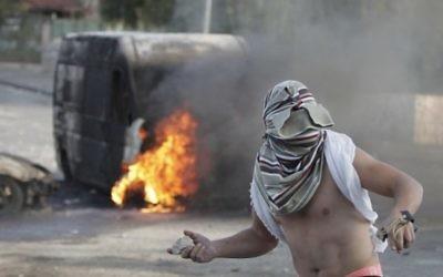 Un Palestinien masqué jette des pierres à la police israélienne à Jérusalem-Est - 30 octobre 2014 (Crédit : AFP/ Ahmad Gharabli)