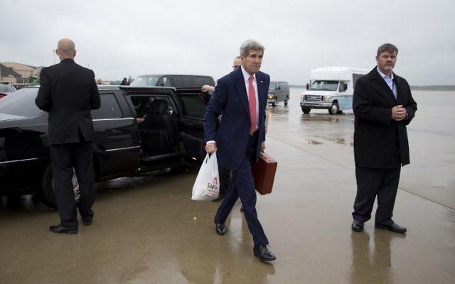 Le Secrétaire d'Etat américain John Kerry sur le tarmac dans la base aérienne Andrews dans le Maryland, en route pour le Caire, le 11 octobre 2014. (Crédit : Carolyn Kaster/Pool/AFP)
