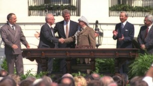 Bill Clinton regarde Yitzhak Rabin et Yasser Arafat se serrer la main lors de la signature historique des accords d'Oslo - 13 septembre 1993 (Crédit : courtoisie GPO)