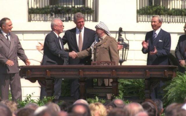 Bill Clinton regarde Yitzhak Rabin et Yasser Arafat se serrer la main lors de la signature historique des accords d'Oslo, le 13 septembre 1993. (Crédit : courtoisie GPO)