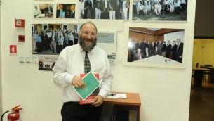 Dov Maïmon présentant une brochure du JPPI traduite en chinois  (Crédit : Aurèle Medioni/Times of Israel)