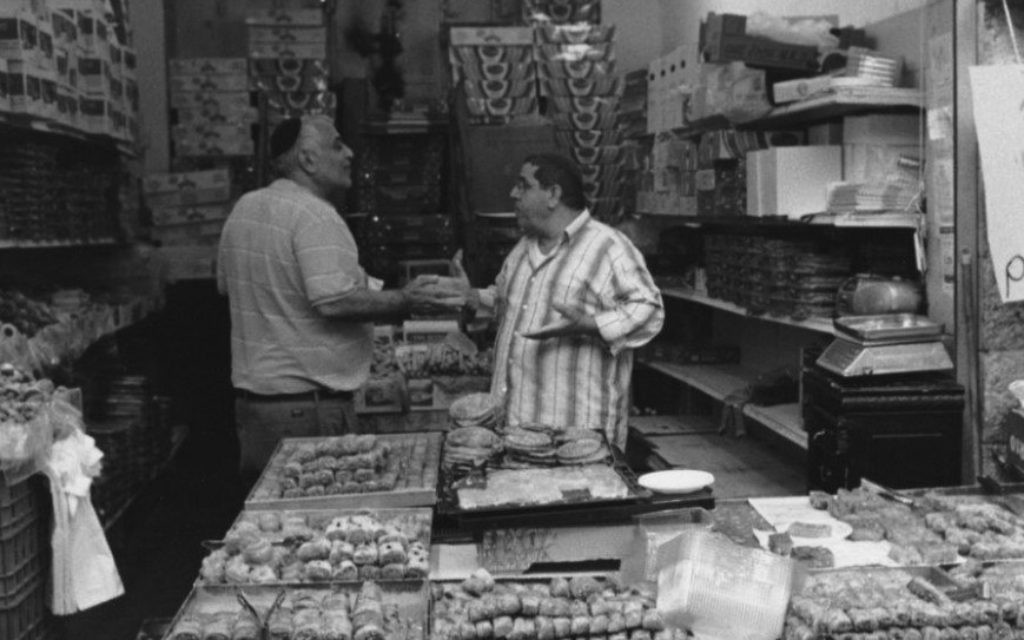 'Discussion in a pastry shop, Mahane Yehuda Market, Jerusalem' [Discussion dans une pâtisserie au marché Mahane Yehuda, Jérusalem] (Crédit : Paul Margolis)