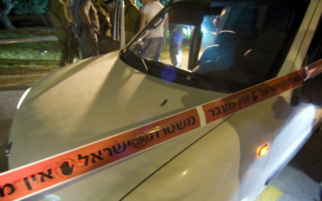 Une voiture entourée d'un cordon de sécurité de la police (Crédit : Flash 90)