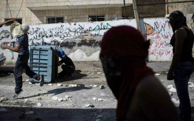 Des Palestiniens masqués s'affrontent avec des policiers israéliens à Abu Tor - 30 octobre 2014 (Crédit : Hadas Parush/Flash90)