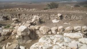 Le sol rocheux et le mur à Tel Burna, avec LE kibboutz Beit Nir en arrière-plan. (Crédit : Ilan Ben Zion / Times of Israël)
