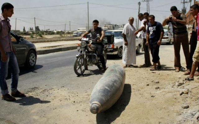 Des Palestiniens devant une munition non explosée sur une rue à Deir El-Balah dans la bande de Gaza - 1 août 2014 (Crédit : Mostafa Ashqar / FLASH90)