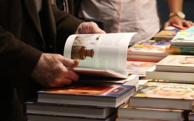 Un homme parcourt un livre à la Foire du livre de Francfort (Crédit : AFP/Daniel Roland)