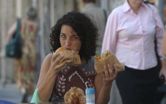 Une femme mange un falafel qui a la réputation internationale d'être rempli de fibres végétales. (Crédit : Orel Cohen / Flash90)