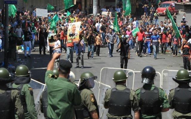 Des Palestiniens jettent des pierres vers les forces de sécurité palestiniennes, qui bloquent la route à un poste de contrôle israélien dans le centre de la ville d'Hébron, en Cisjordanie, le 22 août 2014, suite à une manifestation de soutien au Hamas. (Crédit : AFP / Hazem Bader)