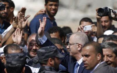 Le Premier ministre de l'Autorité palestinienne Rami Hamdallah (C) salue les gens lors d'une visite dans le quartier Chajaya la ville de Gaza, le 9 O octobre, 2014. (Crédit : Saïd Khatib / AFP)