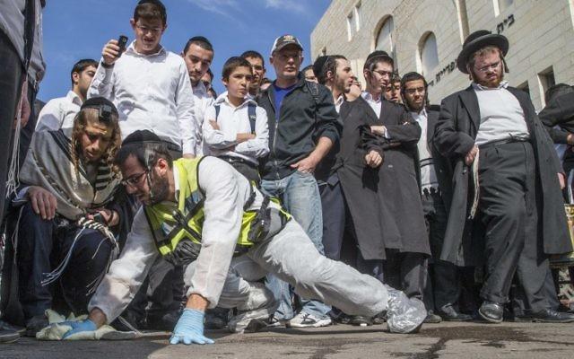 Des Israéliens regardent le lieu de l'attentat terroriste contre la synagogue d'Hart Nof - 18 novembre 2014 (Crédit : Jack Guez/AFP)