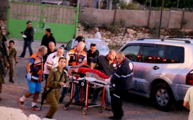 Le personnel de sécurité et de secours israéliens vus avec le terroriste qui a été abattu après une attaque au couteau mortelle à un arrêt de bus à l'entrée de Alon Shvut, le 10 novembre, 2014. (Crédit : Gershon Elinson / Flash90)