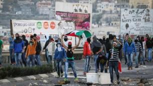De jeunes Arabes jetant des pierres et agitant des drapeaux palestiniens à l'entrée du village arabe de Kafr Kanna le 8 novembre 2014. (Crédit : Hadash Parush/Flash90)