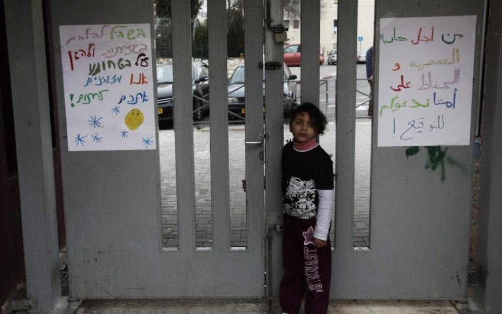 Une enfant arabe devant l'entrée d'une école où l'on peut lire des mots de haine (Crédit : Kobi Gideon/Flash90)