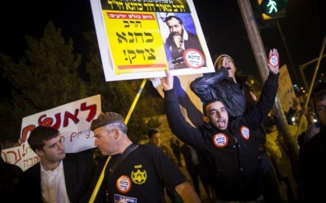 """Un homme tient une affiche où l'on peut lire """"Kahane avait raison"""" sur le site d'une attaque terroriste à Jérusalem le 5 novembre, 2014. (Crédit : Yonatan Sindel / Flash90)"""