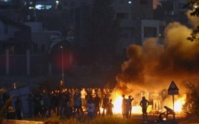 Jeunes Palestiniens jetant des pierres tsur des policiers israéliens devant le village de Kafr Kanna au nord d'Israël, le 9 novembre 2014 (Crédit : Flash90)