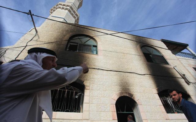 Des Palestiniens inspectent une mosquée qui a été incendiée dans le village d'al-Mughayir, en Cisjordanie près de l'implantation juive de Shilo, le 12 novembre, 2014. (Crédit : STR / Flash90)