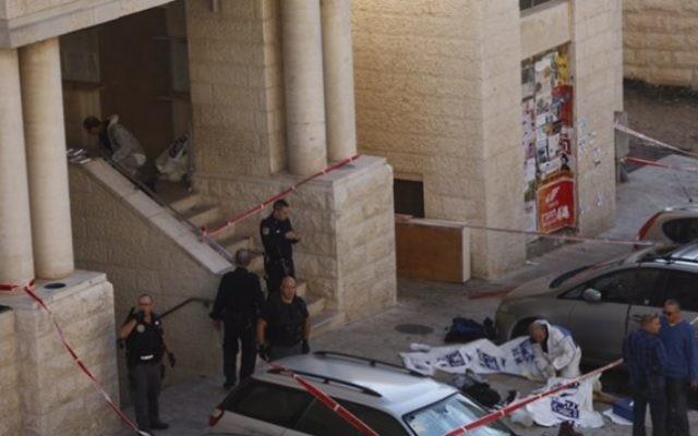 La police israélienne à l'extérieur de la synagogue Kehilat Yaakov à Jérusalem après une attaque terroriste le 18 novembre 2014. Les corps des deux terroristes sont recouverts de plastique (Crédit : Yonatan Sindler / FLASH90)