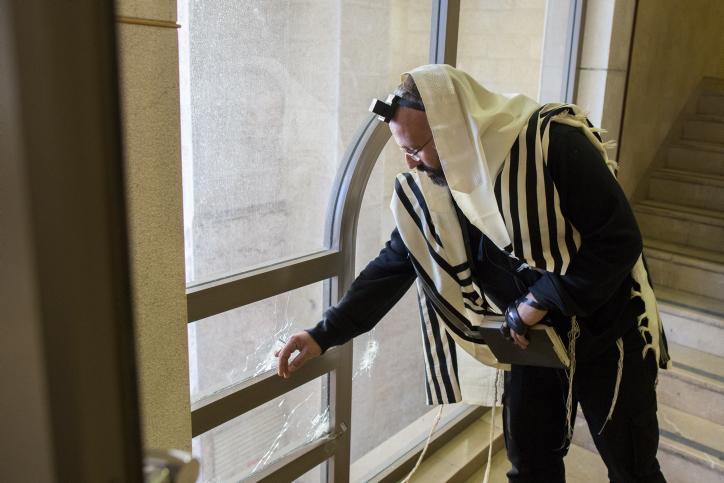 Un homme ultra-orthodoxe examine un trou laissé par une balle à l'intérieur de la synagogue suite à une attaque terroriste qui a tué 5 personnes la veille à Har Nof (Crédit : Yonatan Sindel/Flash90)