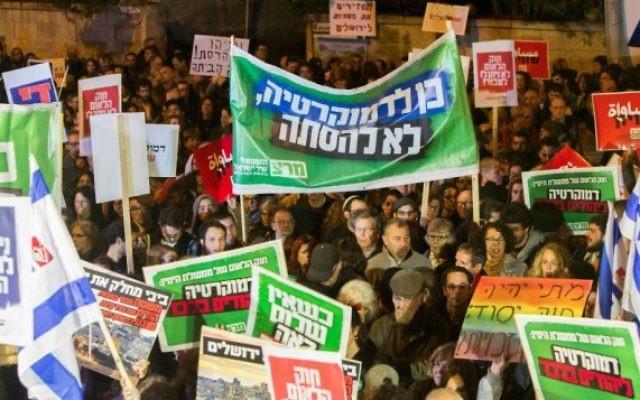 """Des militants de gauche brandissent des pancartes et des drapeaux alors qu'ils protestent contre le projet de loi """"Etat juif"""" près de la résidence du Premier ministre à Jérusalem le 29 novembre, 2014. (Crédit :  Yonatan Sindel / Flash90)"""