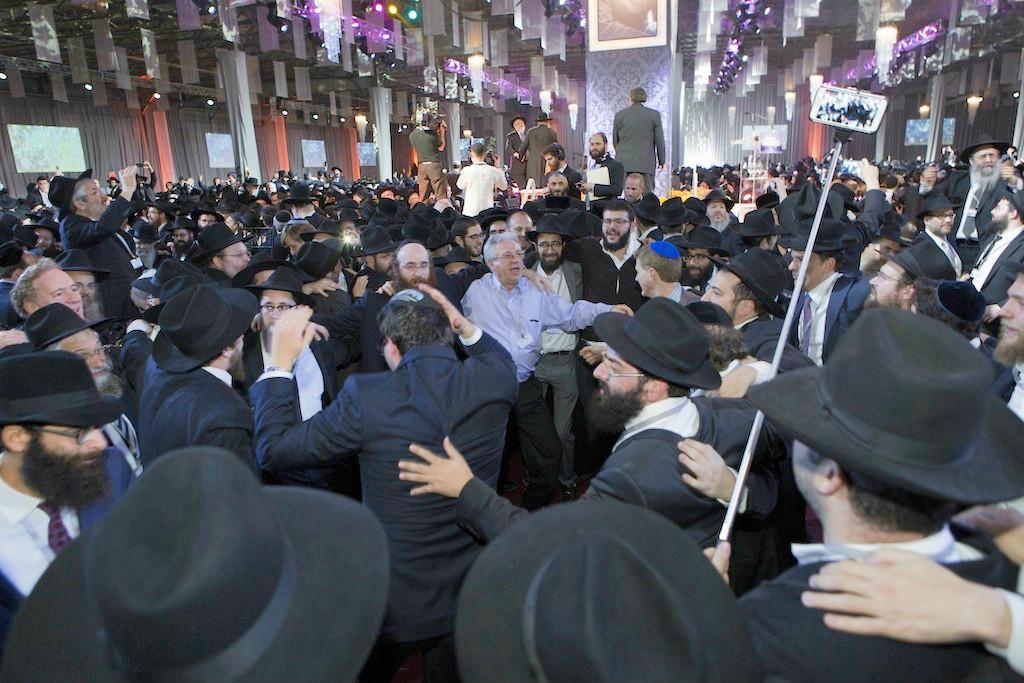 Les émissaires dansant en cercle à la conférence (Crédit : Adam Ben Cohen/Chabad.org)